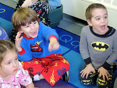 Two boys pajamas, one dressed as Batman.