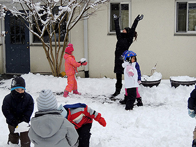 Kids and a teacher playing in the snow.